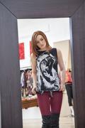 Peilikuva nuori nainen yrittää vaatteita muotiputiikeissa Kuvituskuvat