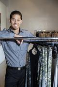 Muotokuva onnellinen nuori mies seisoi vaatteita teline muodin putiikki Kuvituskuvat