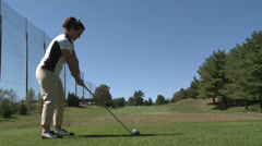 Female golfer missed hitting ball off tee Stock Footage