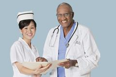 Portrait of happy health care professionals with medical report over light blue - stock photo