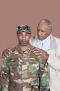 Portrait of African American male US Marine Corps soldier with father over brown Stock Photos