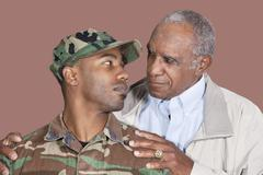 Father and US Marine Corps soldier looking at each other over brown background Stock Photos