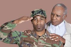 Portrait of US Marine Corps soldier with father saluting over brown background Stock Photos
