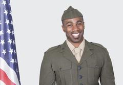 Muotokuva mies Yhdysvaltain sotilaan hymyilee Yhdysvaltain lipun yli harmaa taus Kuvituskuvat