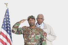 Muotokuva isä Yhdysvaltain merijalkaväki sotilas tervehti Yhdysvaltain lipun yli Kuvituskuvat
