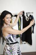 Stock Photo of Portrait of a beautiful mid adult woman standing with top in fashion shop