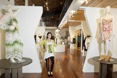 Portrait of a beautiful mid adult woman standing with mannequins in fashion - stock photo