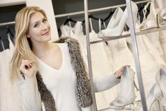 Muotokuva onnellinen nuori nainen seisoi jalkineet seistä morsiamen putiikki - stock photo