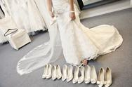 Stock Photo of Low section of young woman standing with variety of footwear in bridal boutique