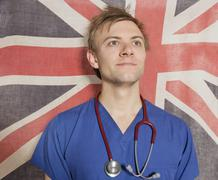Confident male surgeon looking up with British Flag in background Stock Photos