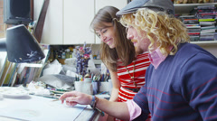 Two young designers or artists collaborating together in their studio - stock footage