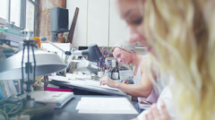 Two young designers or artists working side by side in their studio - stock footage