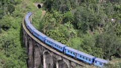 Train crossing bridge and entering tunnel Stock Footage