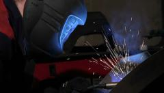 Welder in protective helmet works at factory - stock footage