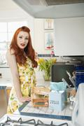 Stock Photo of Portrait of a redheaded woman standing by the kitchen counter