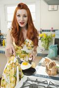 Stock Photo of Portrait of a young redheaded woman cooking omelet