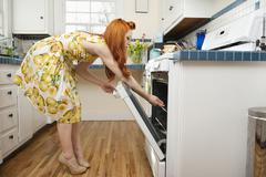 Stock Photo of Side view of young woman opening oven door