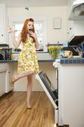 Stock Photo of Full length of a terrified young woman looking at open oven