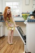 Stock Photo of Full length of a young redheaded woman looking into an open oven