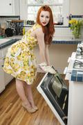 Full length portrait of a young woman standing by an open oven Stock Photos
