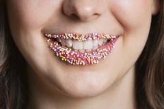Cropped portrait of Middle Eastern woman with sprinkle candy lips Stock Photos