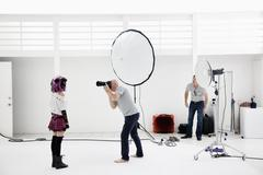 Photographer shooting fashion model in photo shoot - stock photo
