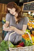 Beautiful young woman listening to mobile phone while making a note of shopping Stock Photos
