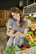 Happy young woman writing on paper while listening to mobile phone in market - stock photo