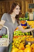 Happy young woman shopping in supermarket for fruits - stock photo