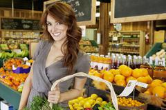 Portrait of a happy brunette woman standing with basket in fruit market - stock photo