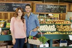 Portrait of a happy young couple in vegetable market - stock photo