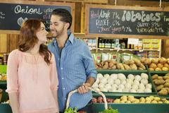 Happy young couple shopping together for vegetables in market - stock photo