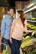 Happy young couple looking at each other while shopping for vegetables in market - stock photo