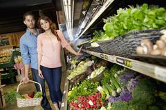 Young couple shopping for vegetables in supermarket - stock photo