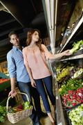 Beautiful young couple shopping together in market - stock photo