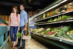 Portrait of young couple standing with vegetable basket in supermarket - stock photo