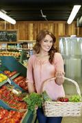 Portrait of beautiful young woman holding basket near tomato stall in market Stock Photos