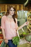 Portrait of beautiful young woman with basket in supermarket Stock Photos