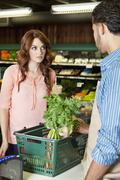 Beautiful young woman looking at store clerk in supermarket - stock photo