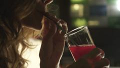 Girl drinks cocktail from the tube at the bar Stock Footage