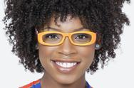 Stock Photo of Close-up portrait of an African American woman wearing glasses over gray