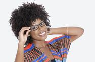 Stock Photo of Portrait of young woman in African print attire wearing glasses over gray