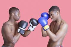 Side view of two African American boxers in fighting stance over pink background Stock Photos