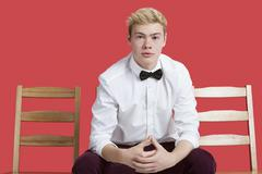 Stock Photo of Portrait of a handsome young man in formal wear sitting on chair over red