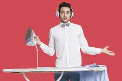 Stock Photo of Portrait of a confused man in formals ironing as he listens to music over red