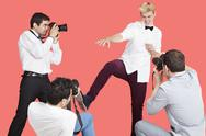 Stock Photo of Paparazzi taking photographs of male actor over red background