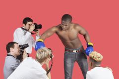 Paparazzi taking photographs of male boxer over red background - stock photo