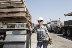 Female industrial worker standing by flatbed truck in timber yard Stock Photos
