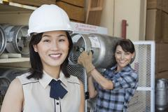 Portrait of woman smiling with female industrial worker carrying propane - stock photo