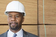 Confident African American male contractor looking away with stacked wooden Stock Photos